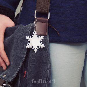 Tasche mit Schneeflocke Reflektor-Anhänger, ideal beim Stadtbummel. Kann leicht an Taschen, Rucksäcken und Jacken befestigt werden.