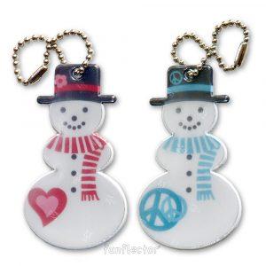 Winterliche Schneemann Reflektor-Anhänger mit Liebes- und Friedensymbol. Für Fußgänger, Radfahrer, Wintersportler und Schneemannbauer. Können leicht an Winterkleidung, Jacken oder Taschen befestigt werden.